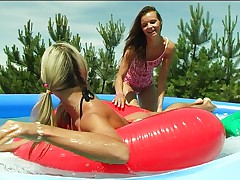 Two girls having fun in inflatable pool 1